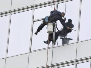 Güvenli ip kullanarak dış cephe için cam temizliği yapan personel